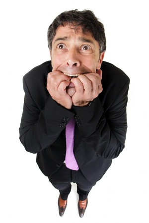 horrified: Quirky high angle portrait with diminishing perspective portrait of a fearful man biting his fingernails in trepidation, isolated on white