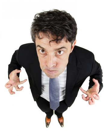 Fun high angle portrait with diminishing perspective of a frustrated angry man glowering up at the camera while making claws of his hands, isolated on white photo