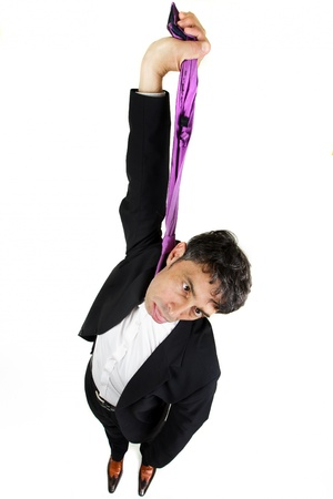 Humorous high angle portrait of a businessman committing suicide holding up his tie as thoughit were a hangmans rope and dangling his head with his tongue protruding, isolated on white photo