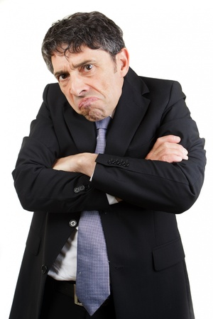 Unhappy businessman standing with his arms folded grimacing and glowering at the camera with a sullen expression, isolated on white Stock Photo - 20573848