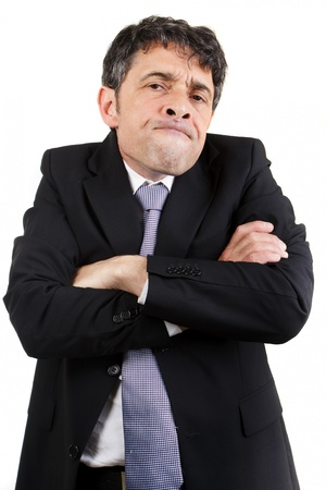 frowns: Businessman with a speculative expression standing frowning at the camera with his arms folded while assessing the situation, isolated on white