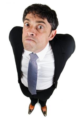 Humoristische hoge hoek volledige lengte portret van een zakenman met een slechte houding schitteren op de camera met een oorlogvoerende expressie en zijn armen achter zijn rug Stockfoto