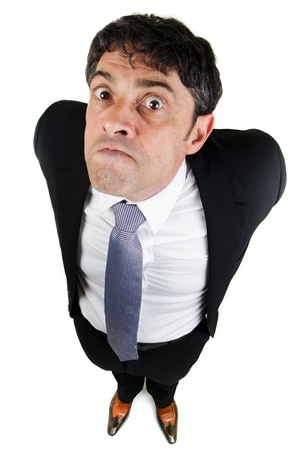 trait: Humorous high angle full length portrait of a businessman with a bad attitude glaring up at the camera with a belligerent expression and his arms behind his back Stock Photo
