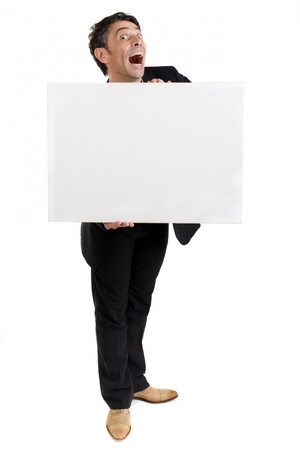 Businessman holding a blank white card or sign in front of his chest with an exaggerated open-mouthed look of amazement, humorous portrait isolated on white Stock Photo - 20573864