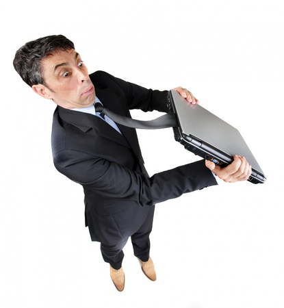 unusual angle: Businessman with his tie caught in his closed laptop computer tugging at it with a look of astonished frustration, , isolated on white