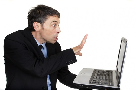 Businessman casting a spell on his laptop holding it in one hand while gesturing with his splayed hand at the screen with a look of intense amazement Stock Photo - 20573840