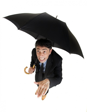 Humorous high angle full length portrait of a businessman sheltering under his umbrella checking on the rain holding out his hand to check for raindrops with a foolish grin, isolated on white Stock Photo - 20573871