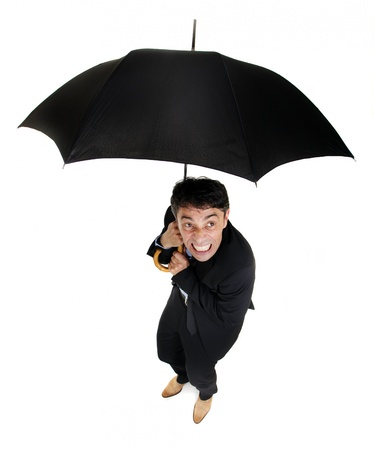 cowering: Humorous high angle full length portrait of a squeamish business cowering under an umbrella as he looks up at the inclement rainy weather around him Stock Photo