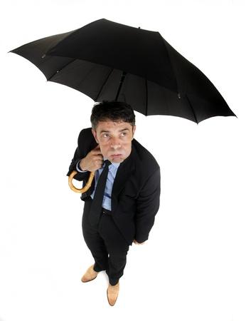 sotto la pioggia: Umorismo alto angolo piena lunghezza ritratto di un uomo d'affari di morose guardando il tempo in piedi sotto il suo ombrello guardando con un'espressione petulante, isolato su bianco