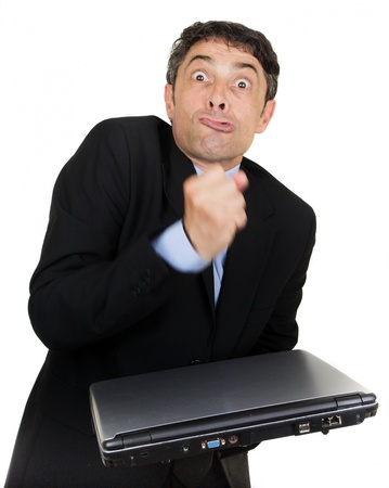 Exasperated man making a fist over his closed laptop computer which he is holding i his hand while grimacing at the camera, isolated on white photo