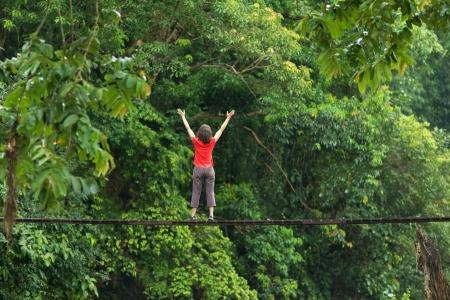 Vrouw ontspannen op houten brug in diepe jungle, Thailand
