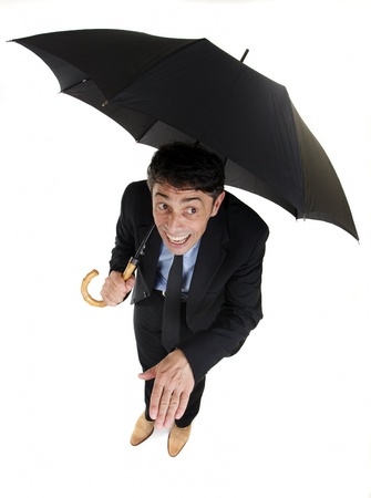 inclement: Humorous high angle full length portrait of a businessman sheltering under his umbrella checking on the rain holding out his hand to check for raindrops with a foolish grin, isolated on white Stock Photo