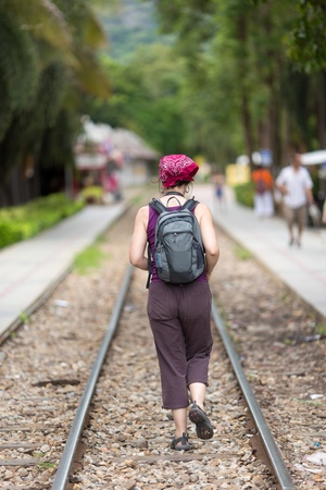 Alone backpacker woman walking on railway photo