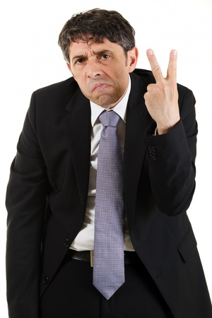 obscenity: Businessman making a rude derogatory v-sign gesture with his hand while grimacing and frowning at the camera, three quarter portrait on white