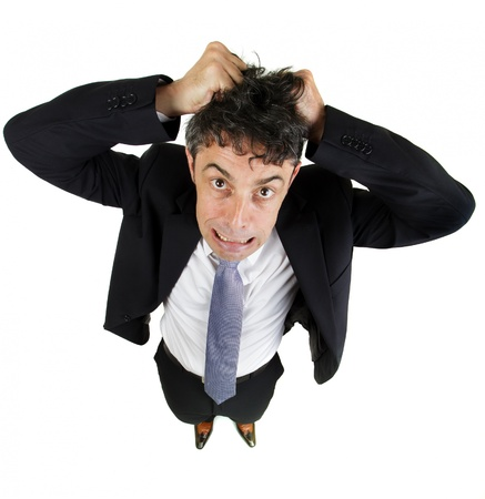 High angle fun portrait of a mature business man tearing out his hair in desperation and frustration isolated on white photo