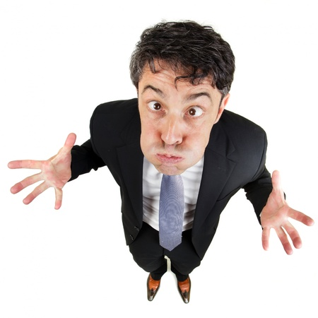 exasperated: Frustrated man holding his breath and wringing his hands in desperation as he standing looking up at the camera with bulging eyes, fun high angle portrait isolated on white Stock Photo