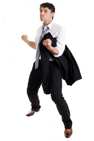 jambes �cart�es: Bellig?rant homme en col?re ramasser un combat permanent avec sa veste sur son ?paule et jambes ?cart?es renfrogn? et mena?ant du poing