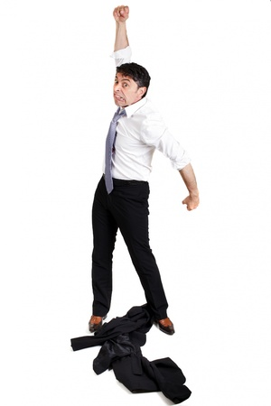 irked: Mature businessman throwing his jacket down on the floor in frustration and anger and raising his fist in the air belligerently isolated on white