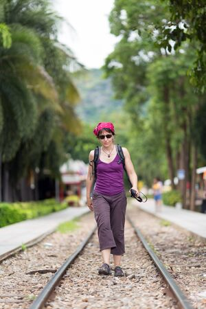Alone traveler woman  walking on railway photo