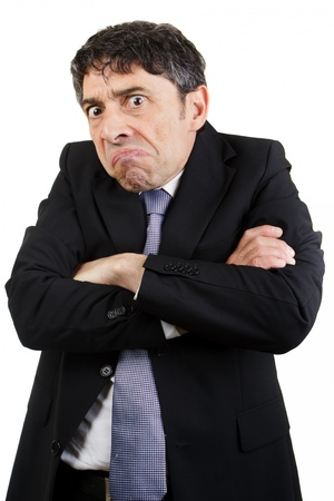 grimacing: Unhappy businessman standing with his arms folded grimacing and glowering at the camera with a sullen expression, isolated on white Stock Photo