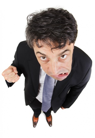 glowering: Humorous high angle full length portrait of an angry businessman glowering from under his eyebrows at the camera while growling and making a fist, isolated on white