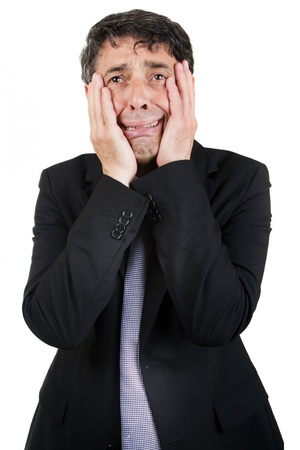 woebegone: Griefstricken businessman holding his face in his hands as he cries to himself with a woebegone expression, isolated on white Stock Photo