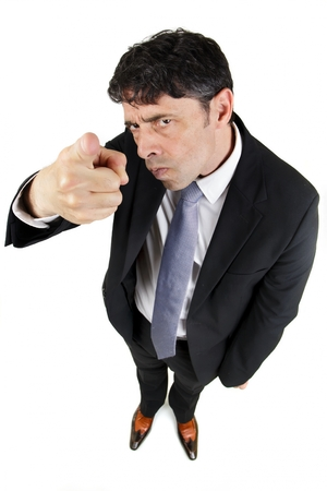 incriminate: Humorous high angle portrait of a man in a business suit pointing a finger in accusation and blame with a stern uncompromising expression isolated on white Stock Photo