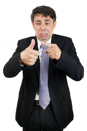 woeful: Tearful business man pointing to his injured thumb with a woeful piteous expression isolated on white Stock Photo