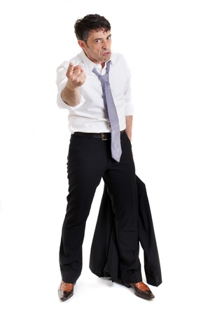 vindictive: Belligerent businessman pointing a threatening finger at the camera in anger with a ferocious expression, full length isolated on white Stock Photo
