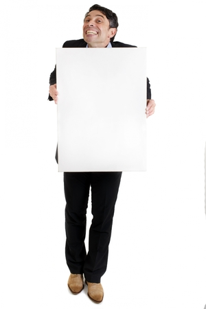 insincerity: Businessman with a cheesy toothy grin of insincerity and obsequiousness holding a blank white sign with copyspace for your text or advertising, full length isolated on white