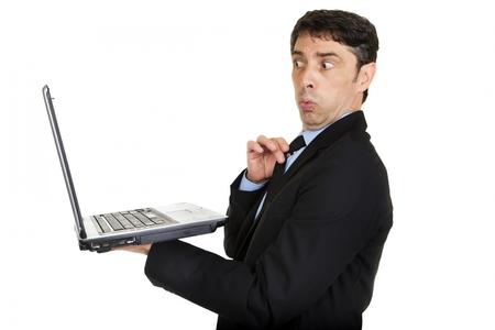 Man kijkt verbaasd en beledigd als hij kijkt naar het scherm van zijn handheld laptop computer en ziet iets risque of beledigende geïsoleerd op wit Stockfoto