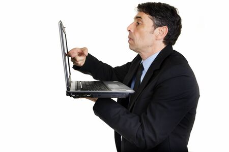 handholding: Side view of a serious businessman tapping his laptop screen with his finger as he stands holding it in his hand, upper body portrait isolated on white Stock Photo