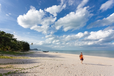 One woman walking on wild tropical Khanom beach under a blue and cloudy sky, Thailand photo