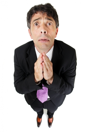 begging: Humorous high angle full length portrait of an expressive desperate businessman praying in supplication pleading for help isolated on white