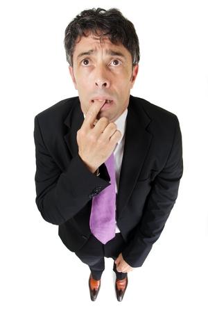 Comic Portrait von einem hohen Perspektive eines vergesslich oder ignorant Geschäftsmann, der mit seinem Finger umklammert zwischen den Zähnen und einem besorgten Ausdruck, isoliert auf weiß Standard-Bild - 22285666