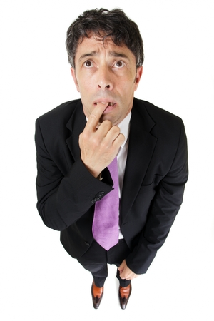 Comic portrait from a high perspective of a forgetful or ignorant businessman standing with his finger clasped between his teeth and a worried expression, isolated on white Foto de archivo