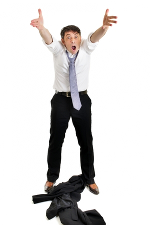 Mature businessman throwing his jacket down on the floor in frustration and anger and raising his arms in the air belligerently isolated on white photo