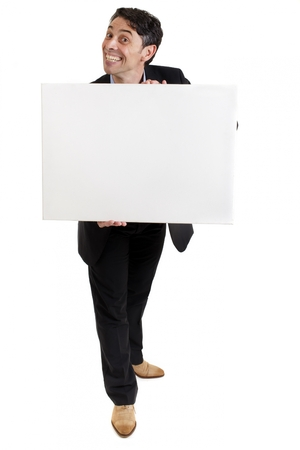 Smart, middle-aged businessman with a cheesy insincere toothy grin holding a blank white sign in his hands with copyspace for your text or advertisement, isolated on white photo