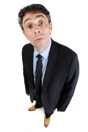 Fun high angle portrait of a middle-aged businessman with a wide eyed enquiring expression or a look of supercilious mockery standing looking up at the camera, isolated on white Stock Photo - 22285676