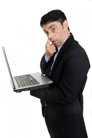 derision: Middle-aged businessman standing sideways handholding his laptop computer gesturing with his finger to his nose in rude derision or because he is picking his nostril, isolated on white Stock Photo