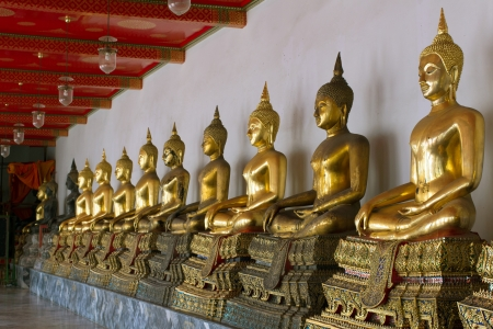 Row of sitting golden Buddha statues in Wat Pho temple, Bangkok, Thailand photo