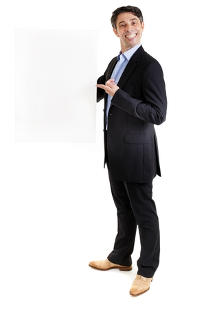 insincere: Suave businessman or salesman with an insincere cheesy toothy grin holding a blank sign and pointing to it with his finger, with copyspace for your text or advertisement Stock Photo