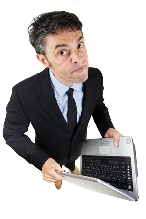 argumentative: Pugnacious businessman holding a laptop computer in his hands standing looking up at the camera with a determined dogmatic expression, isolated on white