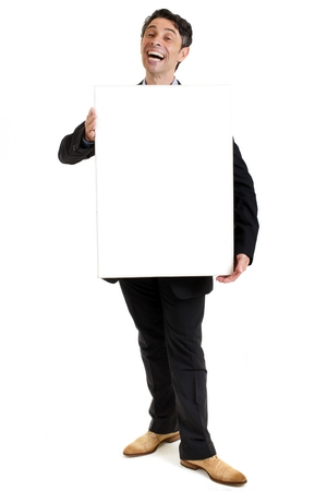 seeks: Hearty salesman with a cheesy wide toothy smile standing holding a blank rectangular sign board in front of his chest as he seeks to promote his product, blank copyspace on the placard for your text