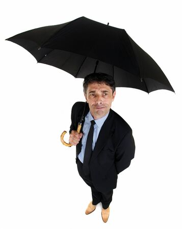 High angle full length portrait of an attractive dapper businessman sheltering under a large black umbrella looking up at the sky with a watchful perplexed expression, on white photo