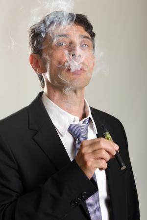 persona fumando: Hombre seguro de mediana edad disfrutando de fumar un cigarrillo electrónico o vaporizador exhalando una nube de humo y mirando a través de los humos con una mirada de la satisfacción