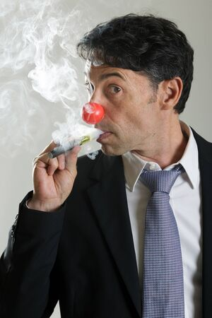 wafting: Middle-aged businessman wearing a red nose like a clown puffing on an e-cigarette standing sideways peering through the fumes with one eye as though guilty or startled