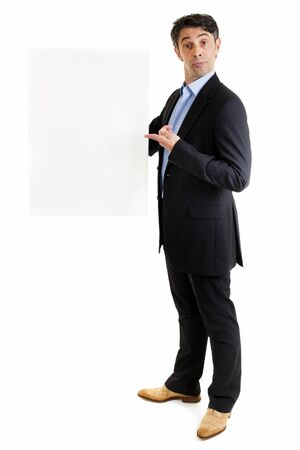 Jaunty salesman or business professional in a stylish suit standing pointing to a blank sign that he is holding in his hand with a comic expression, isolated on white photo