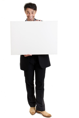 Persuasive middle-aged man with a big smile holding a blank sign in front of his chest as he draws your attention to the copyspace and gives it his endorsement, on white photo