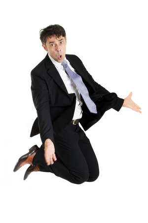 Businessman making an imploring impassioned gesture with outstretched arms while either kneeling on the floor or leaping in the air with his knees bent, isolated on white Stock Photo